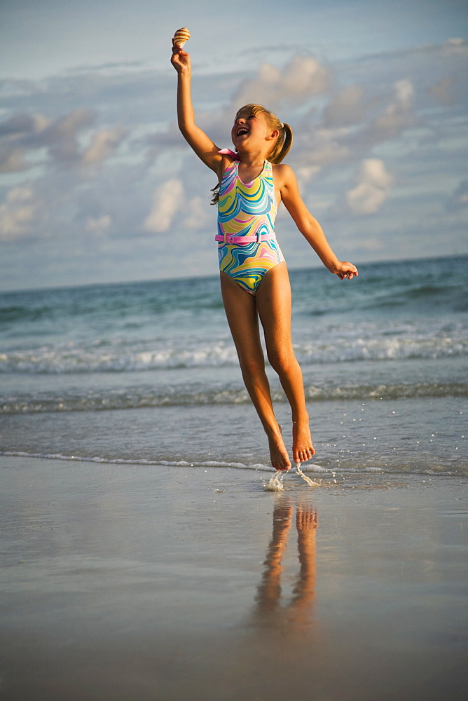 Girl jumping in ocean surf, Florida, United States