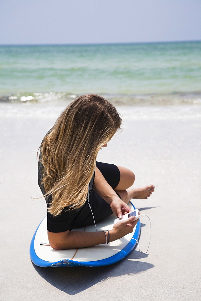 Girl listening to mp3 player on surfboard, Florida, United States