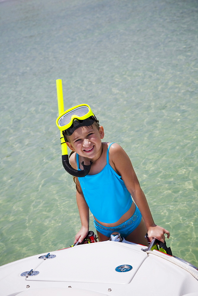 Girl in snorkeling gear climbing onto boat, Florida, United States