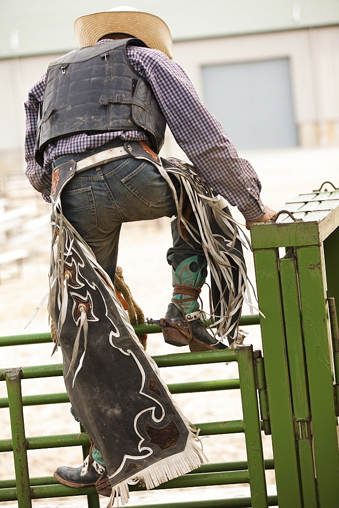 Rodeo cowboy climbing on fence - 1178-12569