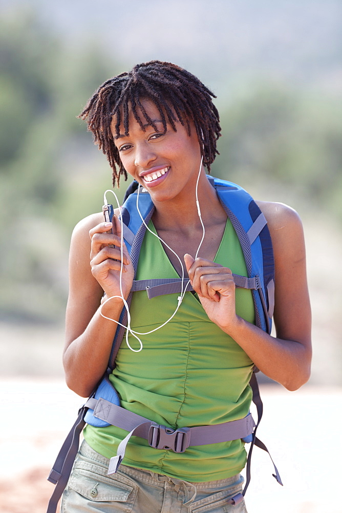 Smiling female hiker listening music
