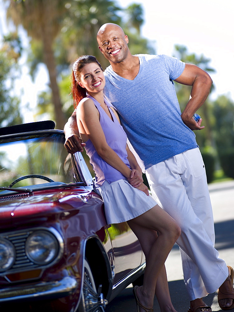 Smiling couple standing together near classic's car