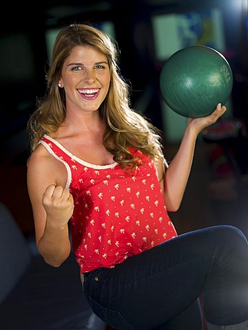 Young smiling woman holding bowling ball