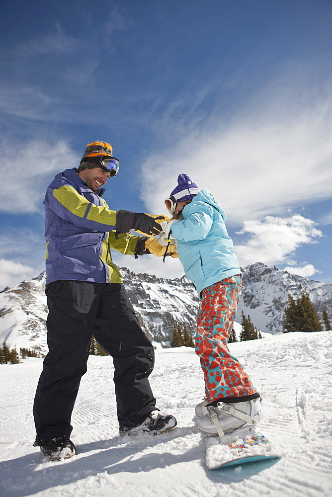 USA, Colorado, Telluride, Father helping daughter (10-11) with snowboard binding