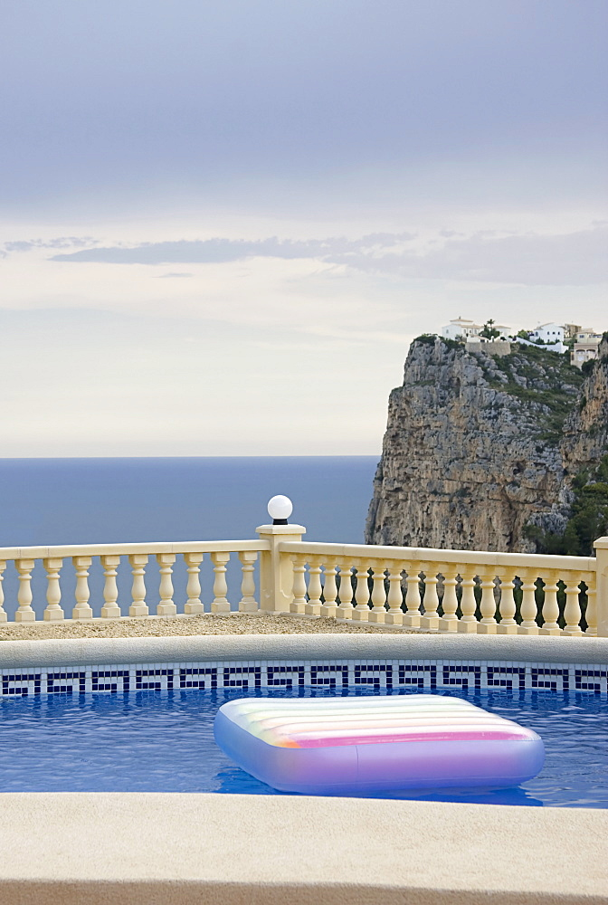 Spain, Costa Blanca, Swimming pool on terrace, sea and cliff in background