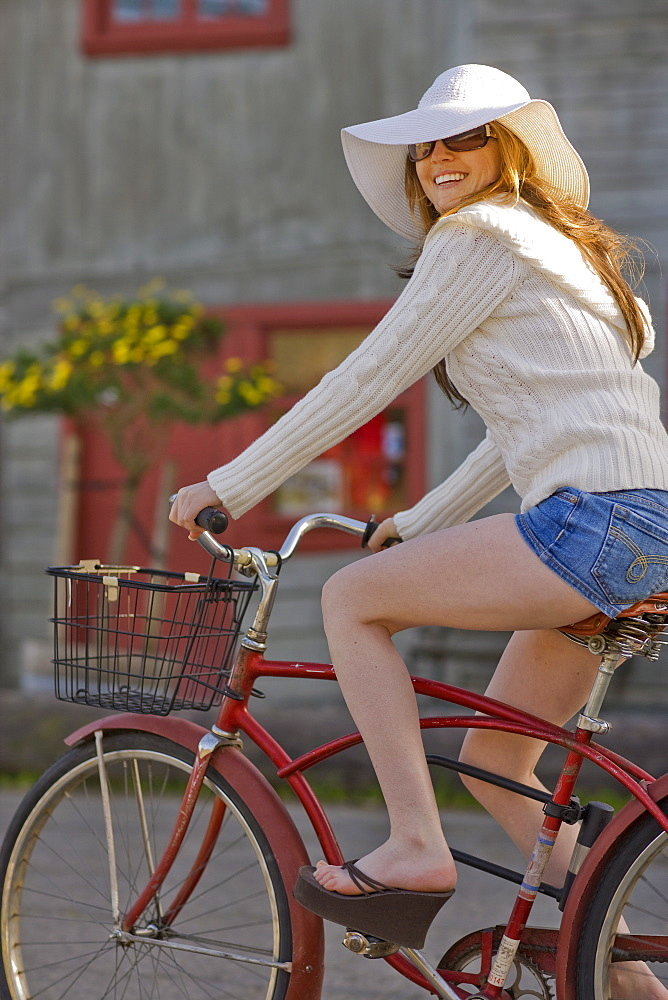 USA, California, Bolinas, Young woman riding bicycle in street