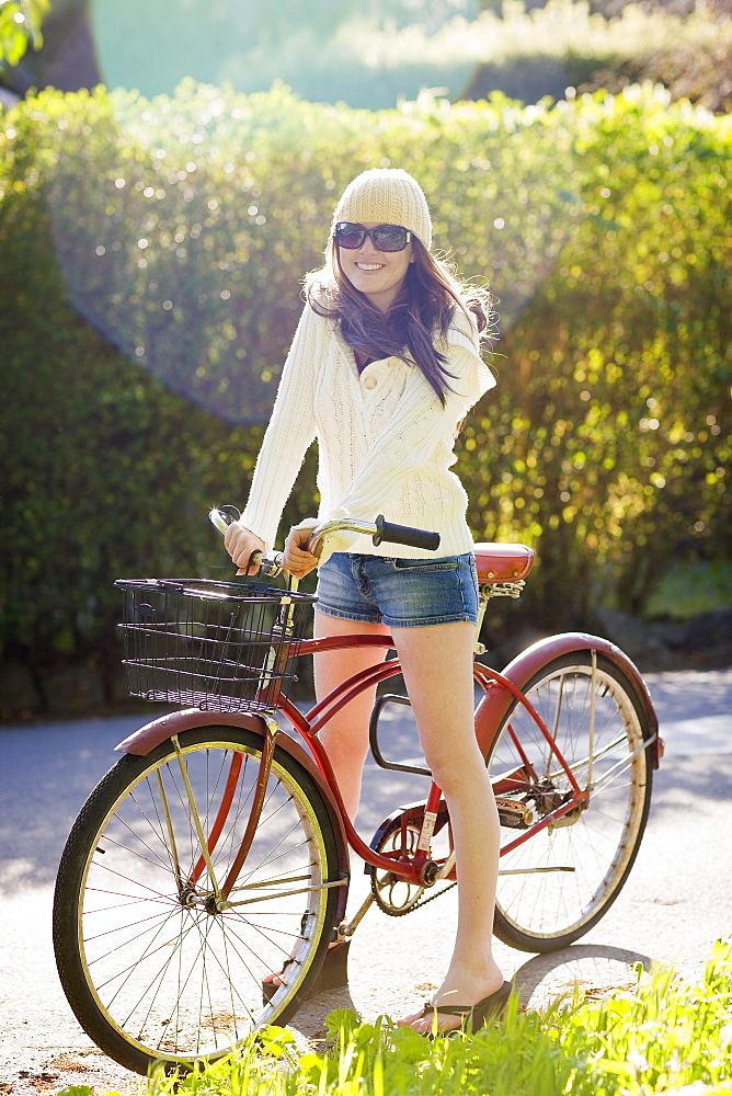 USA, California, Bolinas, Young woman riding bicycle on driveway