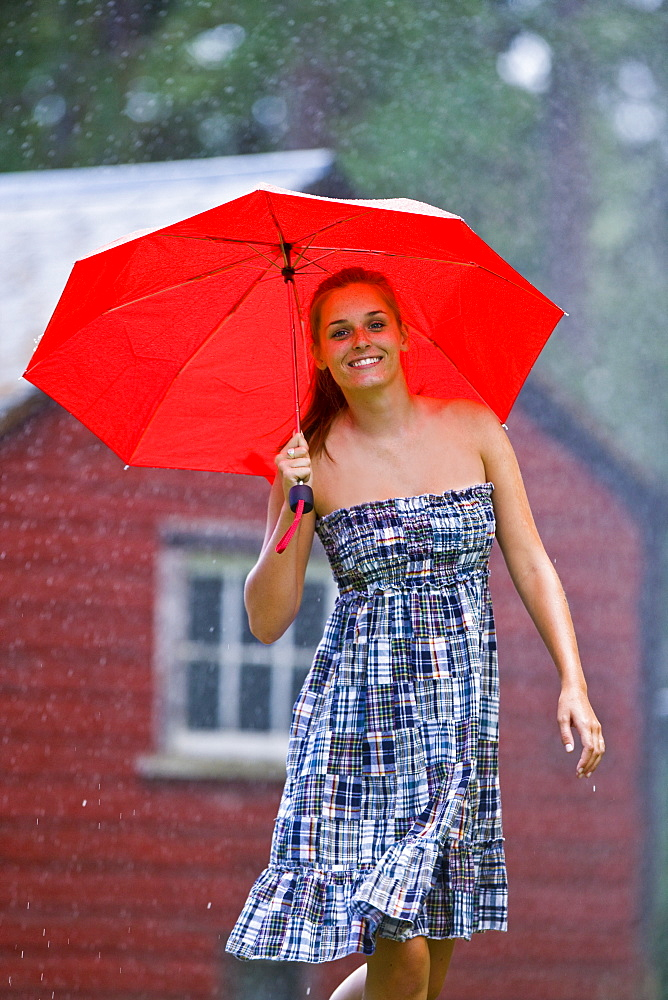 USA, Montana, Whitefish, Portrait of young woman with umbrella in rain