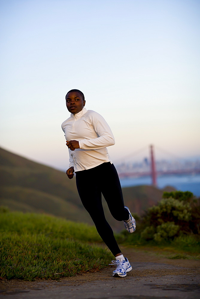 USA, California, San Francisco, Woman jogging, Golden Gate Bridge in background