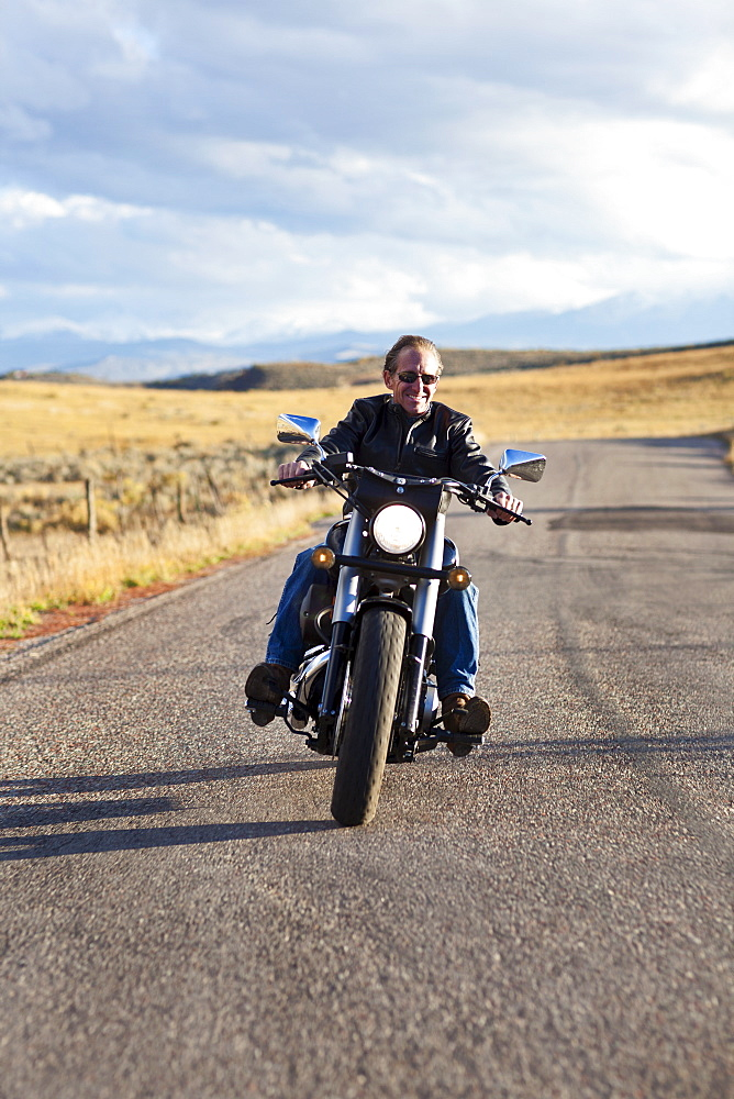 USA, Colorado, Carbondale, Mature man driving motorcycle