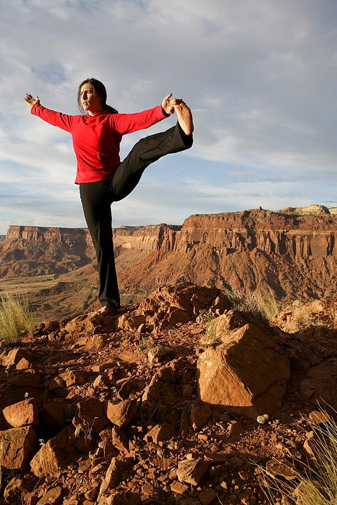 USA, Utah, Canyonlands National Park, woman stretching on rock