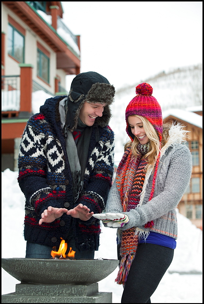 USA, Utah, Salt Lake City, couple warming hands over burner in ski resort