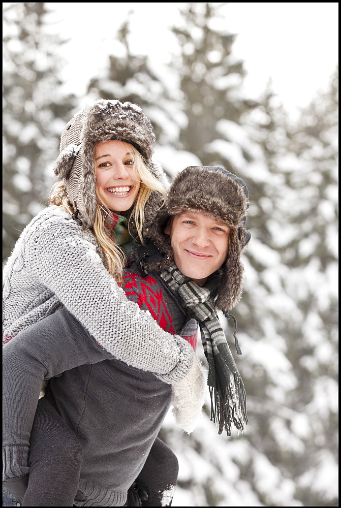 USA, Utah, Salt Lake City, man giving young woman piggy back ride in snow