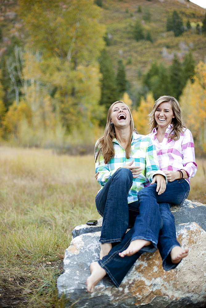 USA, Utah, Sundance, Two young women sitting on boulder and laughing