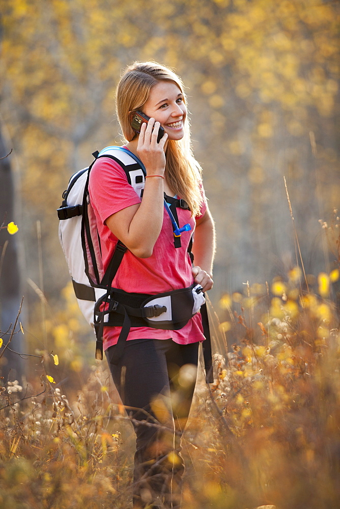 USA, Utah, young woman hiking in forest and talking on mobile phone