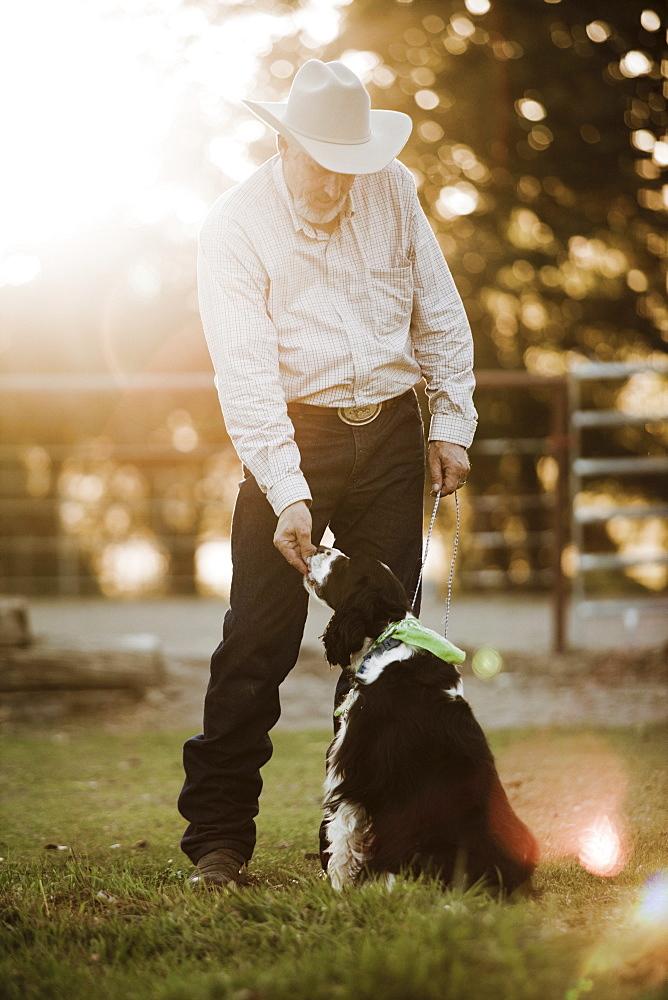 Cowboy feeding dog on ranch