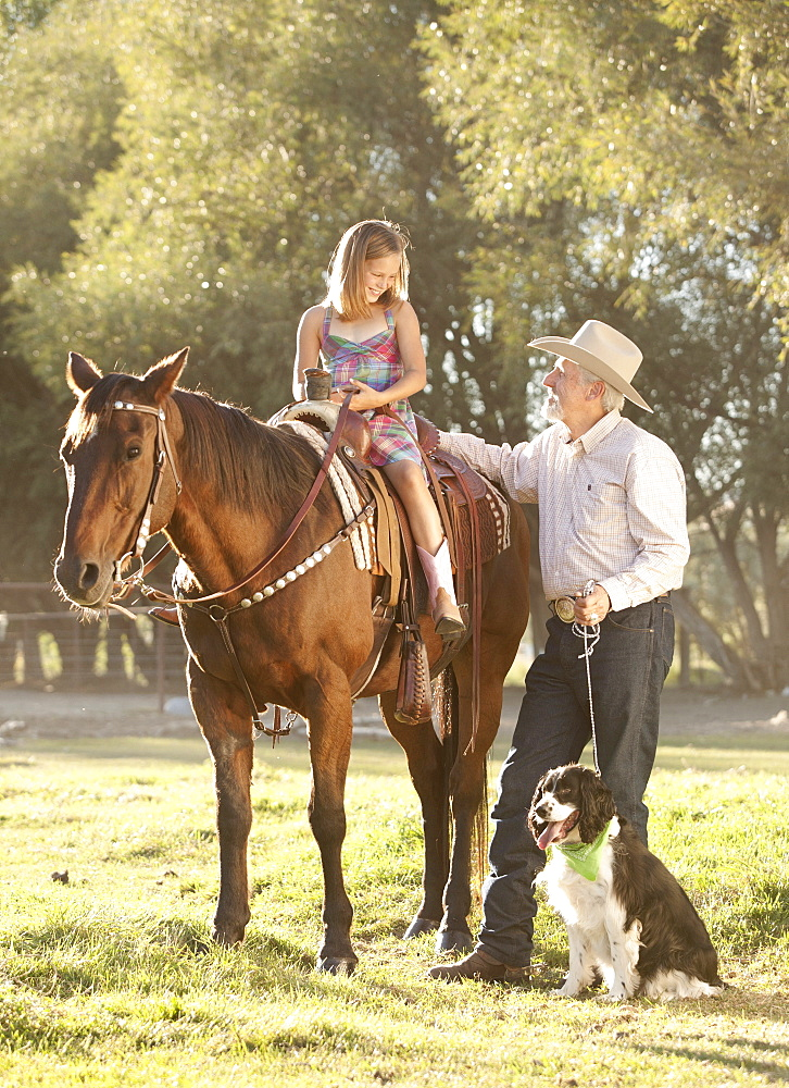 Senior man with dog assisting granddaughter (8-9) horseback riding in ranch