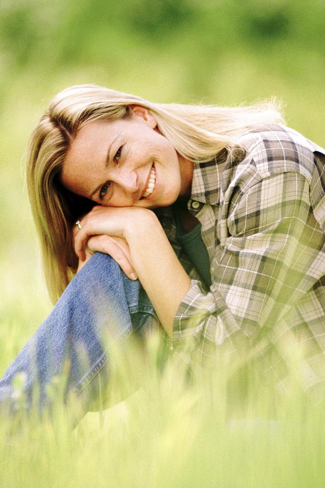Pretty woman relaxing on grass in meadow