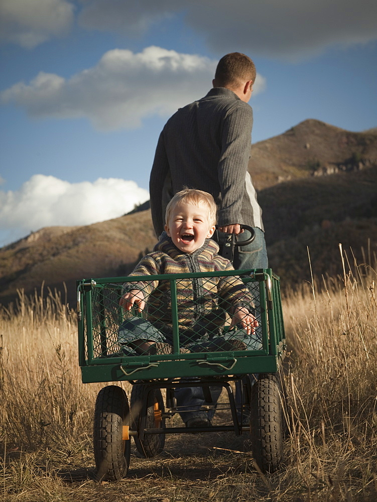 Father pulling son in wagon