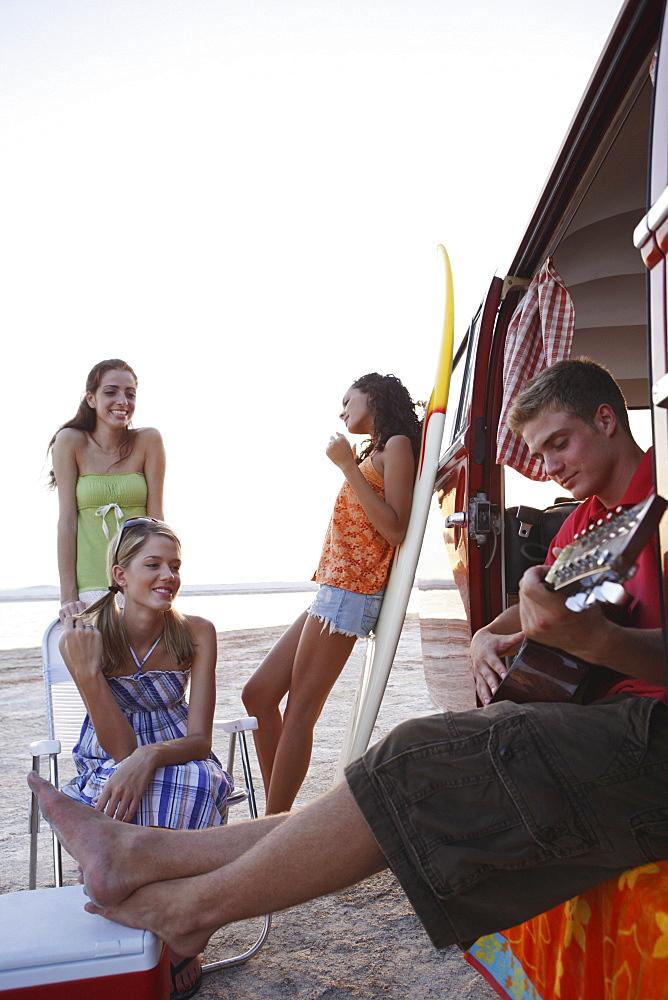 Friends lounging around van on beach