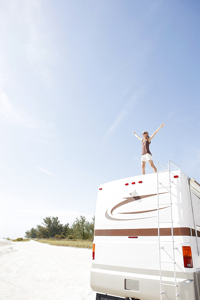 Woman standing on motor home with arms outstretched
