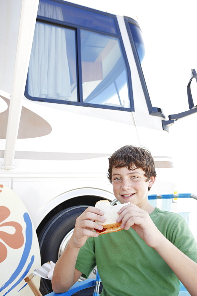 Portrait of boy eating sandwich outside motor home