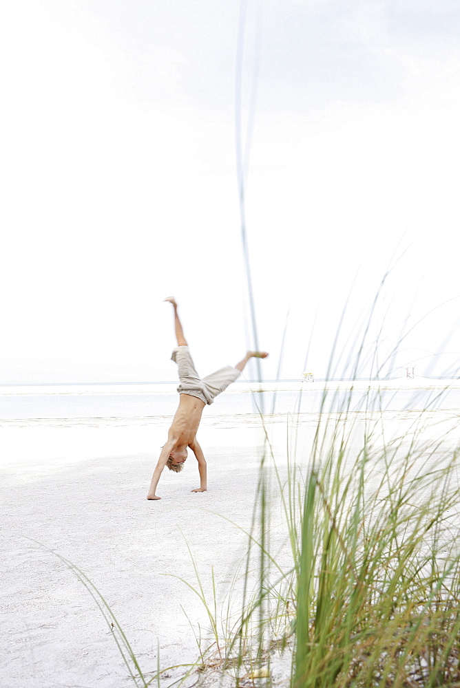 Boy doing cartwheel on beach