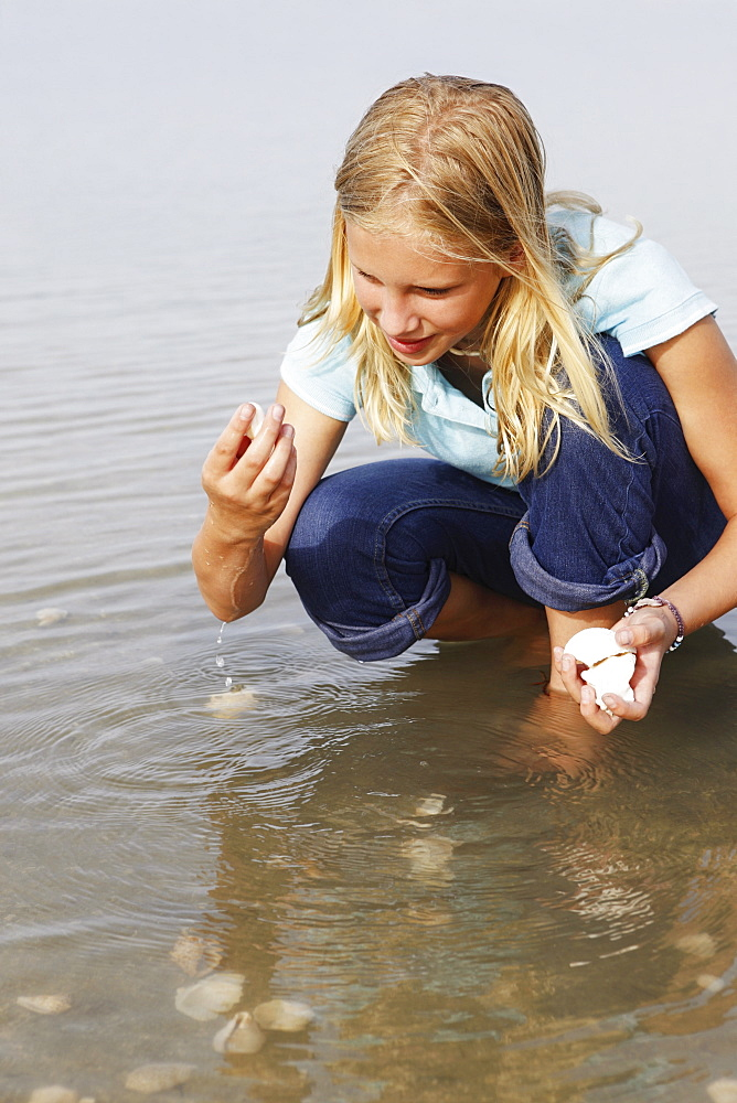 Girl finding seashells in ocean