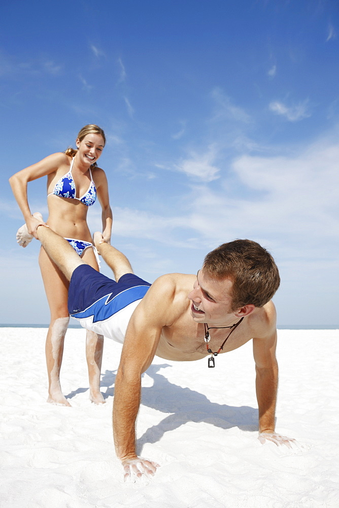 Teenage girl pushing boyfriend on beach