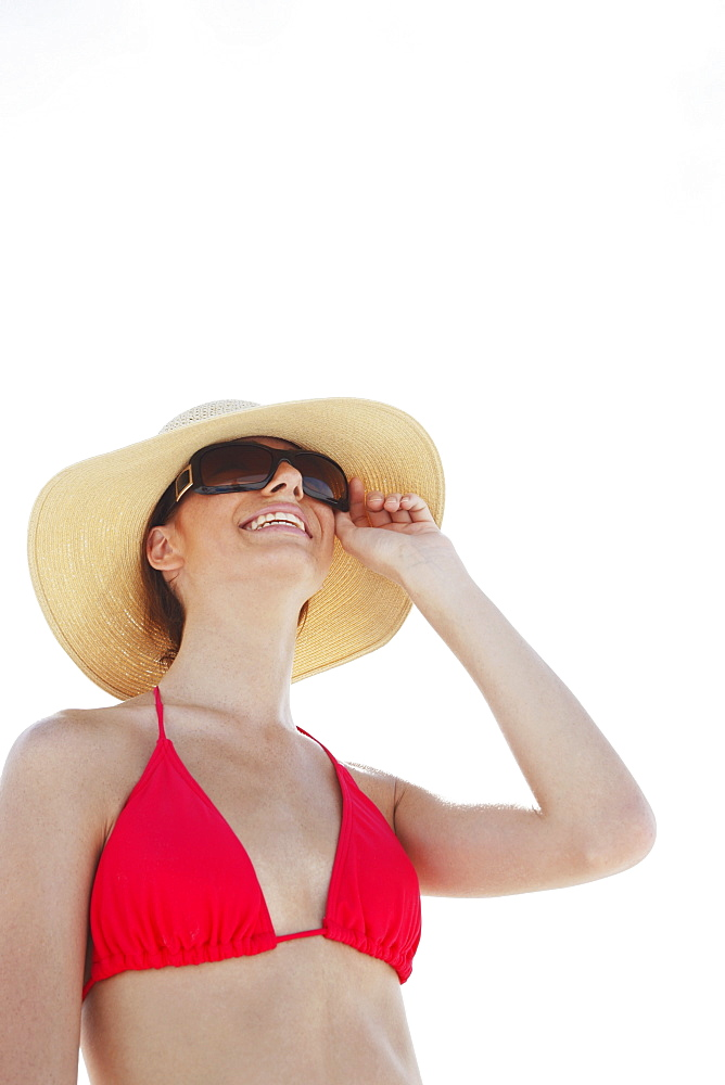Young woman in bikini, protective hat and sunglasses