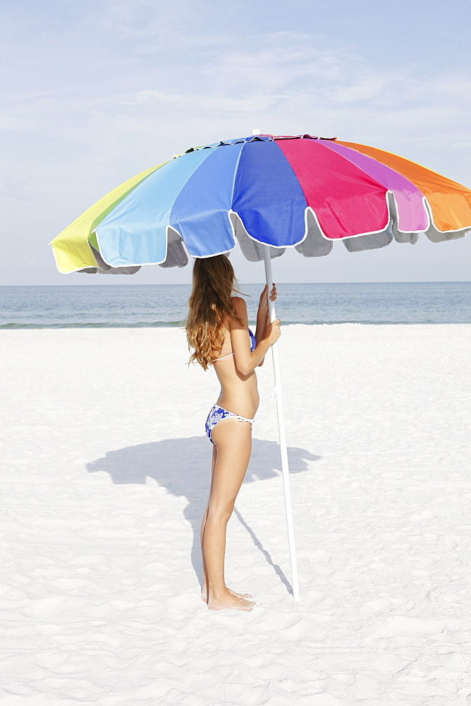 Teenage girl holding umbrella on beach