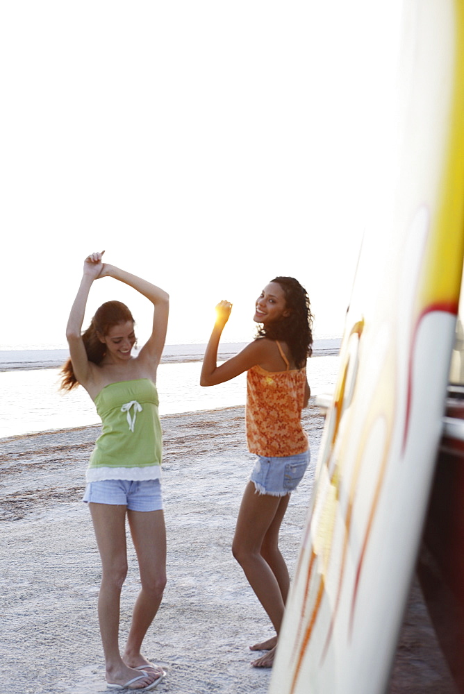 Young women dancing on beach