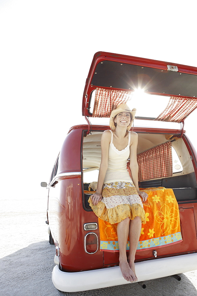Young woman sitting in van on beach