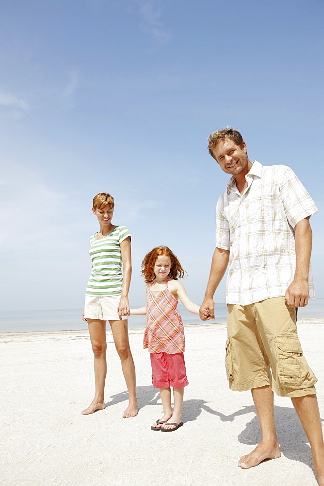 Girl holding hands with mother and father on beach