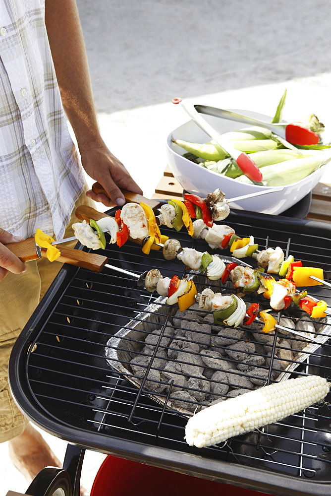 Man grilling shish kebabs and corn