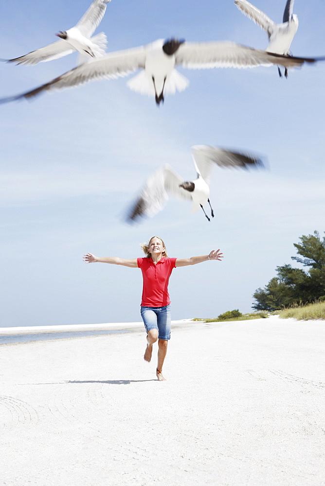 Girl chasing birds on beach