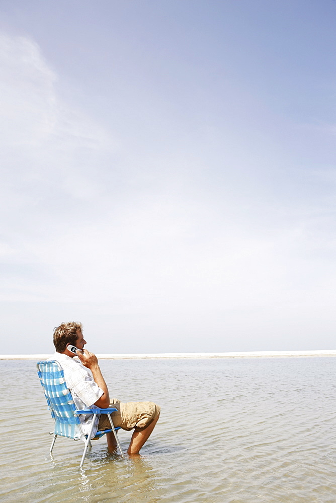 Man talking on cell phone in middle of water