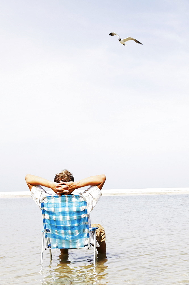 Man relaxing in lounge chair in middle of water