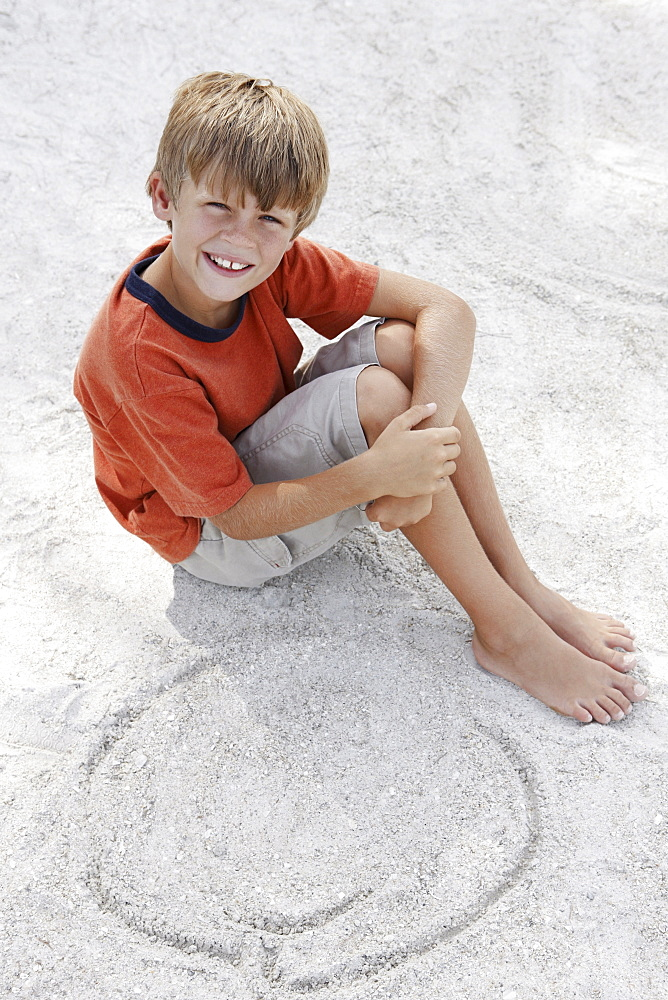 Boy drawing designs in beach sand