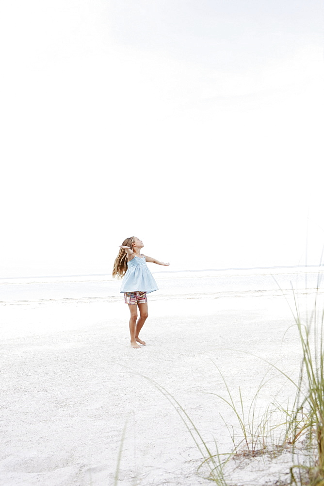 Girl twirling in beach
