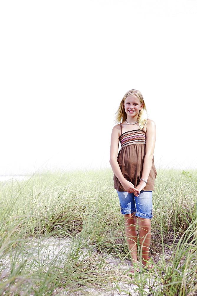 Girl standing on grassy sand dune