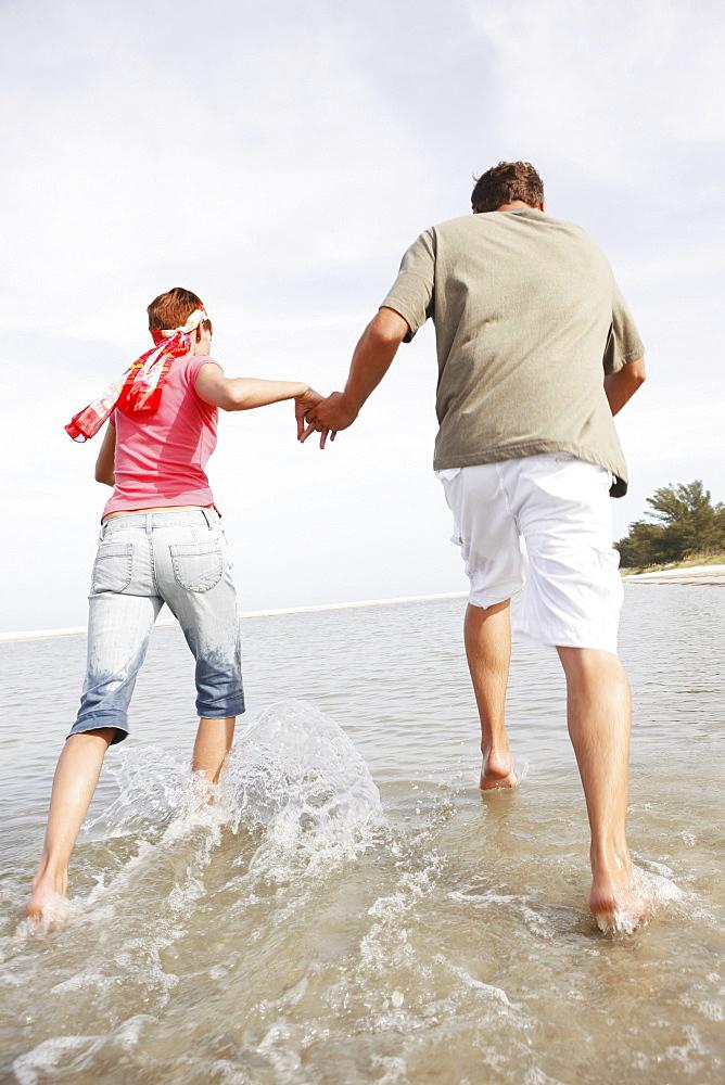 Couple running in ocean