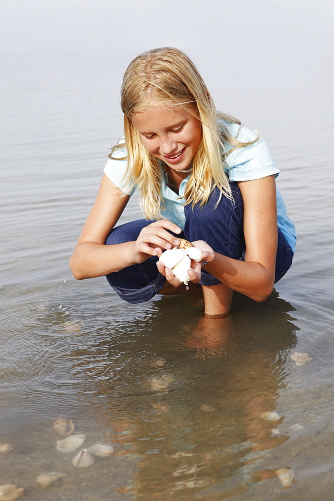 Girl looking for shells in shallow water