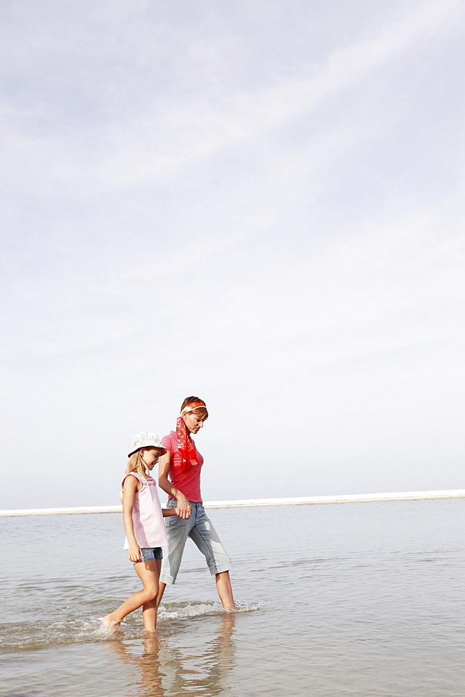 Mother and daughter walking in ocean