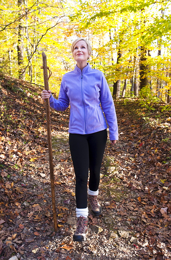 USA, New Jersey, Smiling woman hiking in Autumn forest