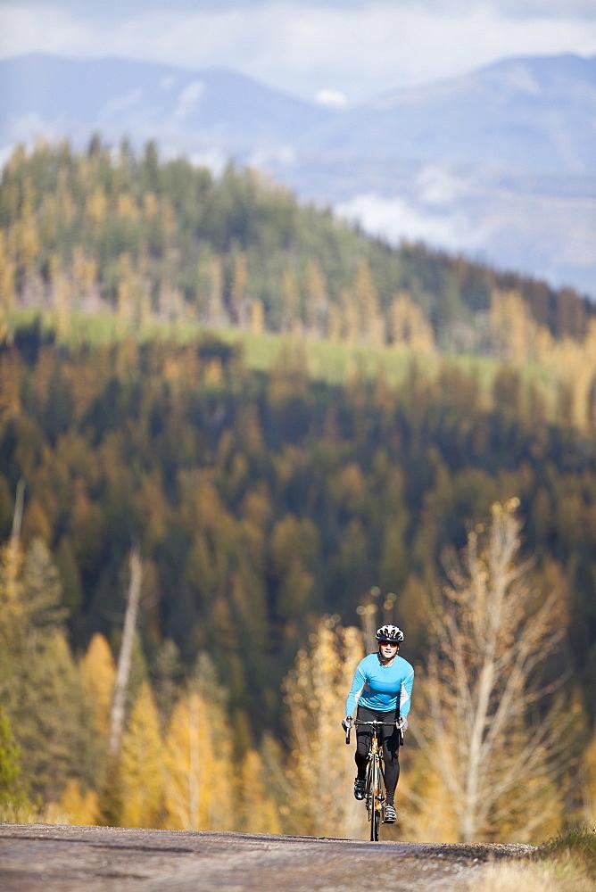 Woman cycling on rural mountain roads in autumn, USA, Montana, Whitefish