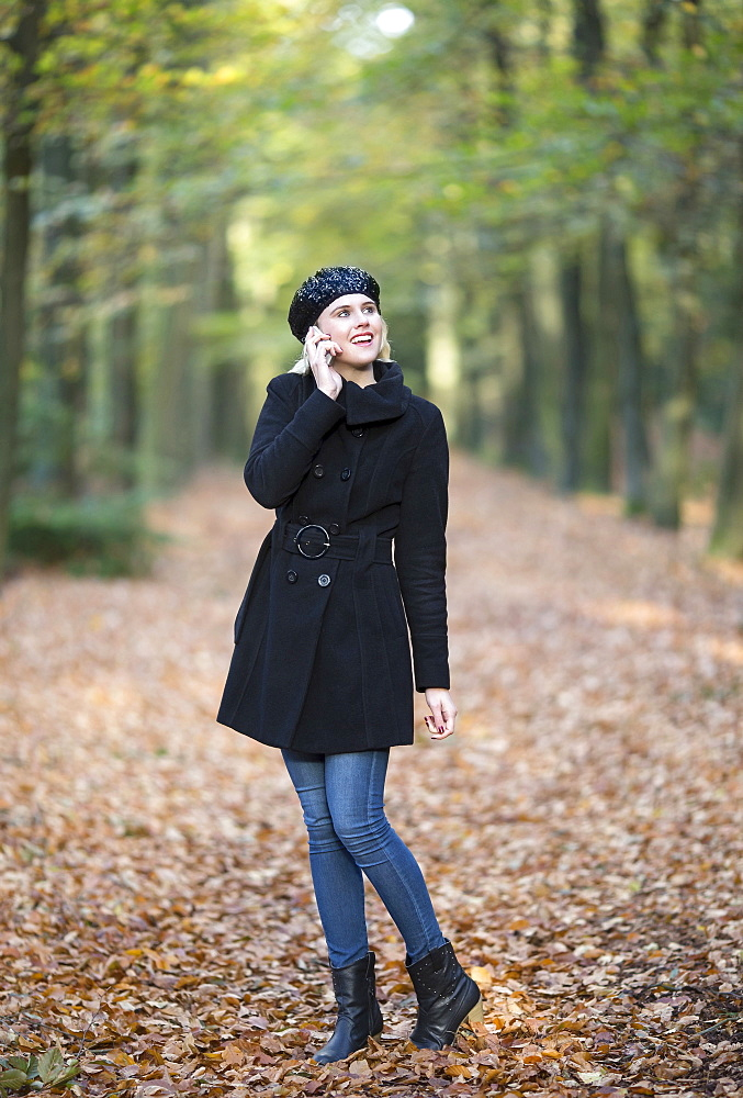 Smiling woman using phone while walking in forest, Goirle Netherlands