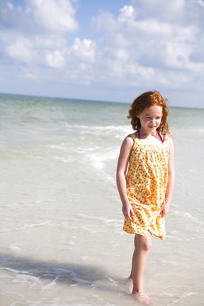 Girl walking through ocean surf