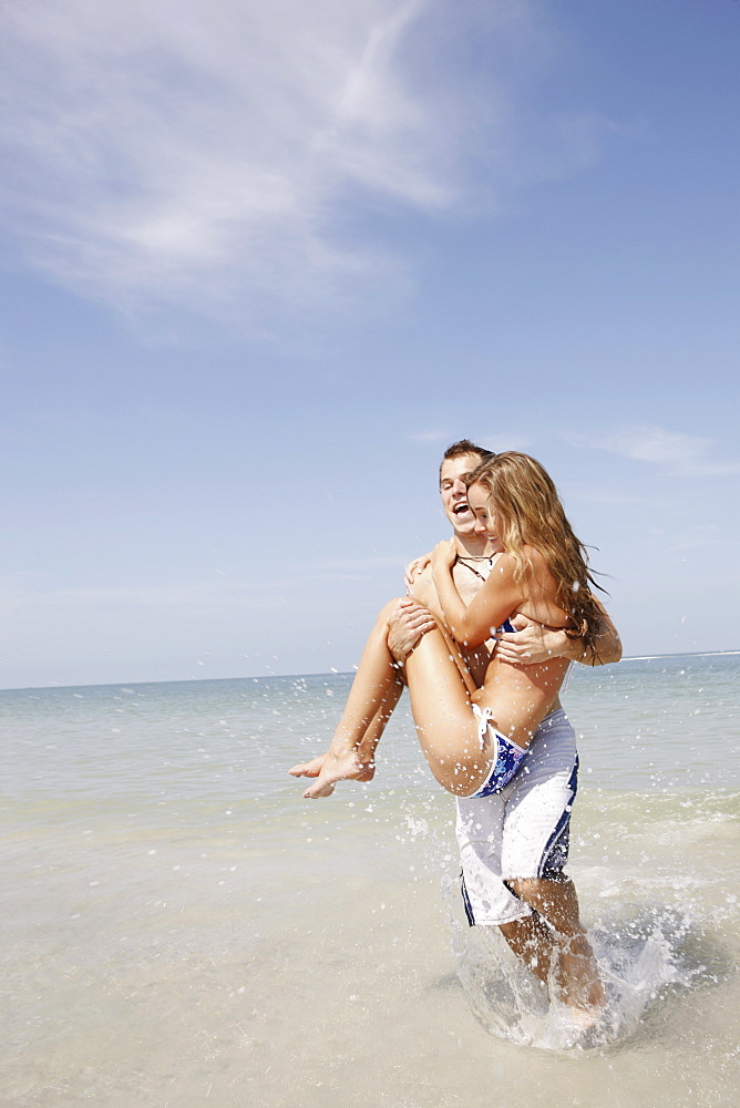 Man carrying girlfriend in ocean surf