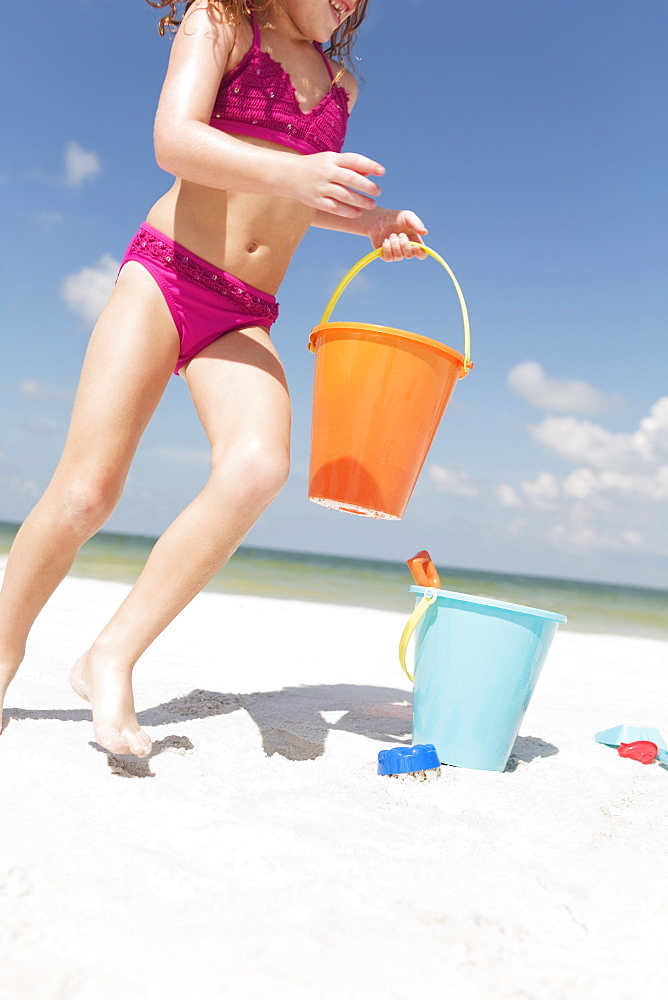Girl playing with sand buckets on beach